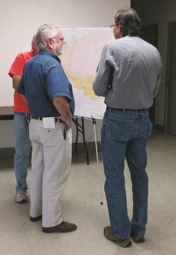 John Stewart and others review maps of Johnson Valley